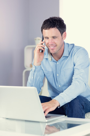 Smiling casual man using laptop and phoning in bright living room photo