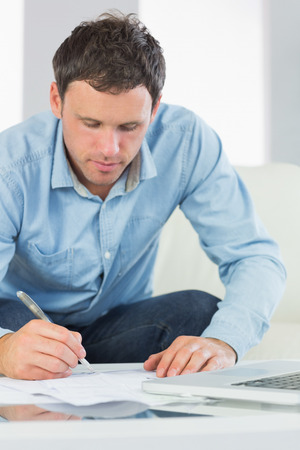 Content casual man writing on sheets paying bills in bright living room photo