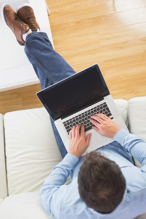 High angle view of casual man typing on laptop with feet on table in bright living room photo