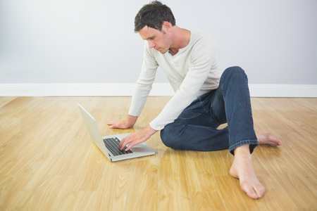 Casual calm man sitting on floor using laptop in bright room