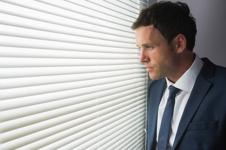 Serious handsome businessman looking out of window in dark room photo