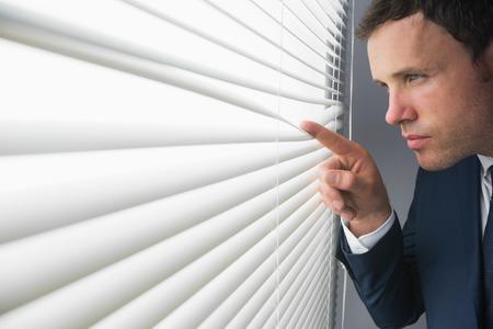 Stern attractive businessman spying through roller blind in dark room Stock Photo