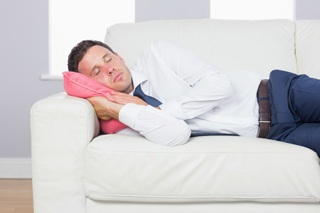 sleep well: Exhausted handsome businessman lying on couch after work at home