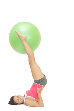 Smiling sporty brunette holding exercise ball between legs on white background photo