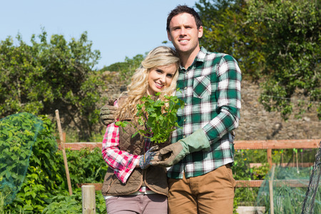 Proud couple posing in a garden holding a shrub smiling at camera photo