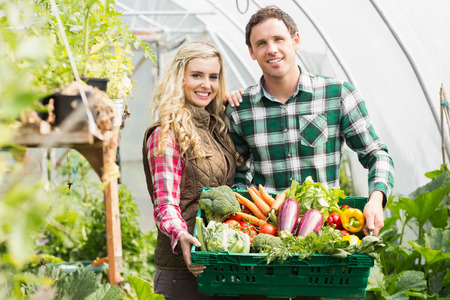 smiling woman in a greenhouse: Young couple standing in their green house presenting vegetables in a basket