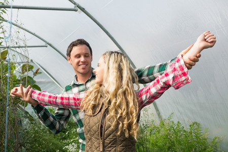 smiling woman in a greenhouse: Sweet couple posing in their greenhouse looking at each other