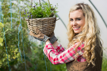 flower basket: Happy woman touching a hanging flower basket in a green house smiling at camera