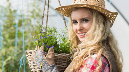 smiling woman in a greenhouse: Smiling blonde touching a hanging flower basket in a green house looking at camera