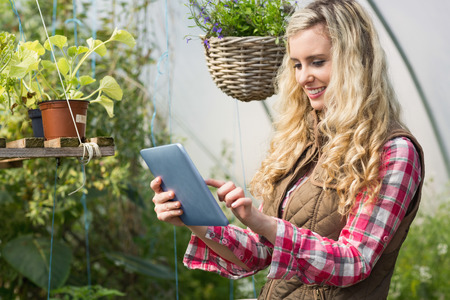 Pretty woman using her tablet in a green house and smiling photo