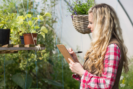 Blonde woman using a clipboard and taking notes in a green house photo