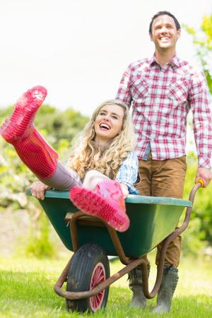 Smiling man pushing his laughing girlfriend in a wheelbarrow in sunny garden