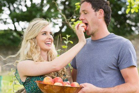 Blonde woman feeding her boyfriend with an apple while laughing photo