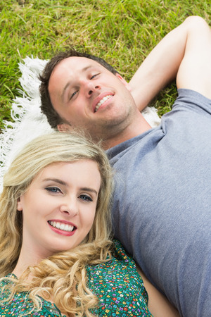 Smiling couple lying on a blanket while looking at the camera photo
