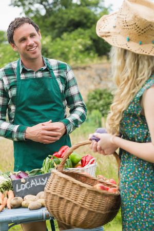 Young farmer selling organic vegetables to pretty blonde at a farmers market photo