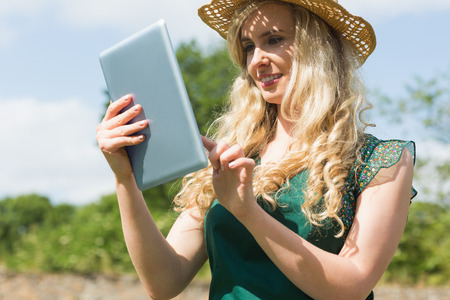 Young female farmer checking her tablet outside on sunny day photo