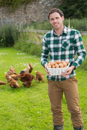 gallina con huevos: Hombre orgulloso mostrando una cesta llena de huevos de pollos detr�s de �l en el jard�n