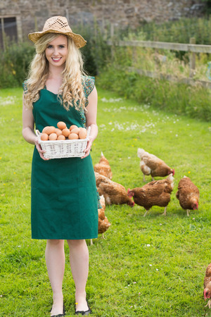 Smiling pretty woman presenting a basket filled with eggs standing in front of her chickens photo