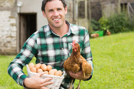 chicken farm: Happy young man holding his chicken and basket of eggs in his garden Stock Photo