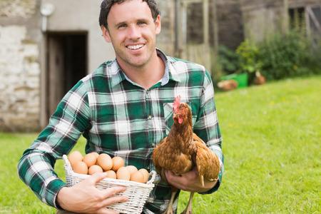gallina con huevos: Hombre joven y feliz celebraci�n de su pollo y cesta de huevos en su jard�n