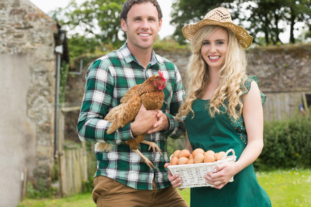 Smiling young couple holding chicken and basket of eggs in their garden photo