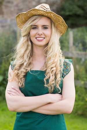 Pretty woman wearing a straw hat folding her arms in her garden photo