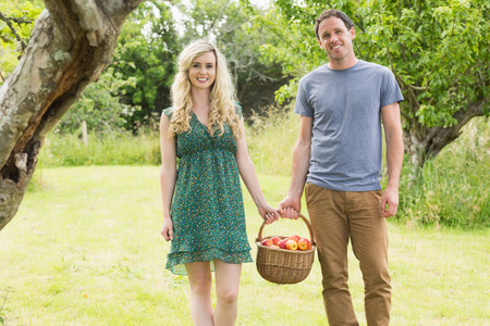 Smiling couple carrying a basket of apples outside in the garden photo