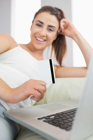 Laughing nice woman using her notebook for online shopping while being in the living room photo