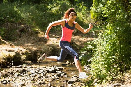 salto largo: Joven deportiva saltando por encima de un arroyo en un bosque en un plazo Foto de archivo