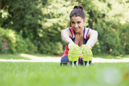 Pretty sporty woman stretching sitting on the ground smiling at camera photo