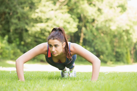 plank position: Serious fit woman doing plank position outside on the grass Stock Photo