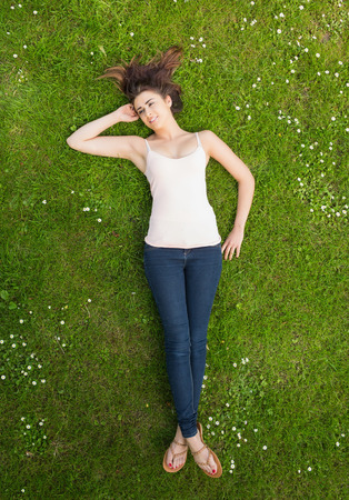 Pretty woman lying on a lawn on a sunny day and looking away photo