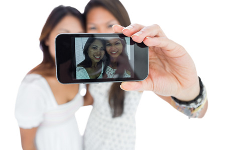 Two smiling asian sisters taking a self portrait using a smartphone photo
