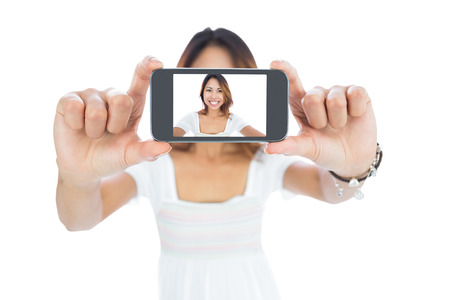 Happy asian woman taking a selfie using her smartphone