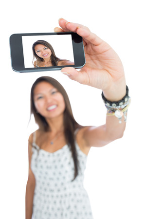 taking photo: Smiling asian woman taking a selfie using her smartphone