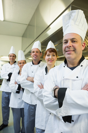 Team of happy chefs smiling at the camera in a kitchen wearing uniforms photo