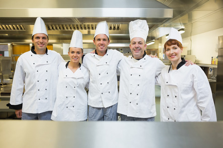 Five happy chefs smiling at the camera in a kitchen wearing uniforms photo
