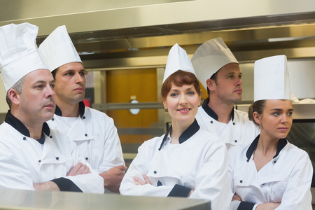 Team of chefs looking away with one smiling at camera standing in a kitchen with crossed arms photo