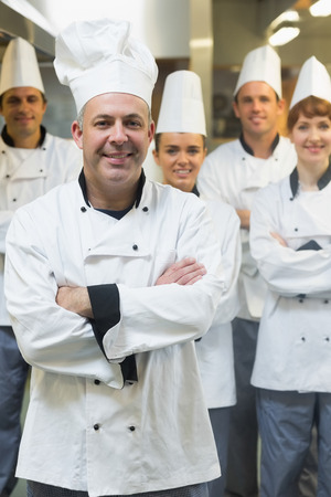 Five chefs wearing uniforms while posing in a kitchen with crossed arms photo