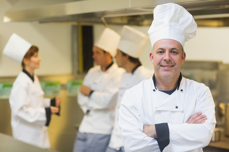 Mature male chef posing proudly in a kitchen with crossed arms and cooks in the background photo