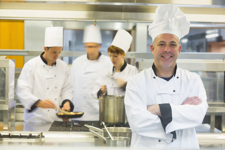 Mature male chef posing with crossed arms while colleagues working in the background  photo