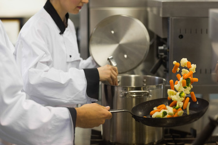 culinary chef: Two chefs working in a busy kitchen at the stove one tossing vegetables