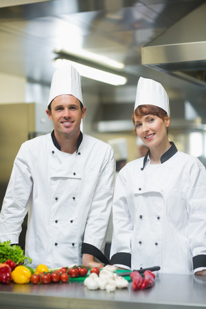 Two young chefs posing in a kitchen behind counter of vegetables photo