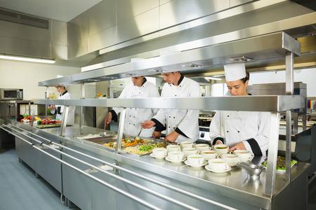 Vier koks werken in een grote keuken op de diensttijd Stockfoto