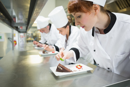 female chef: Chefs standing in a row garnishing dessert plates in the kitchen
