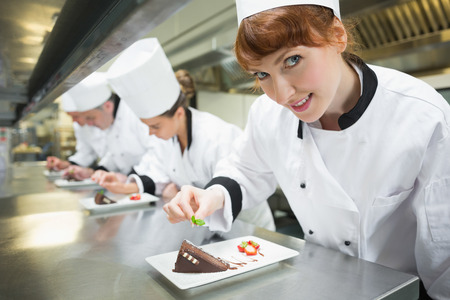 Smiling chef garnishing dessert plate in a busy kitchen photo