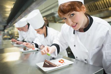 dessert plate: Smiling chef guarnendo piatto da dessert in una cucina occupato Archivio Fotografico
