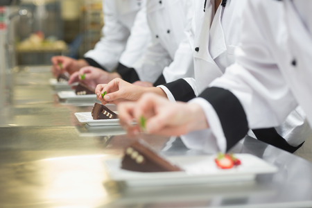Team of chefs garnishing dessert plates in a busy kitchen
