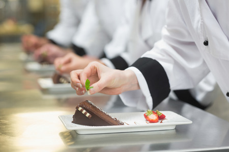Team of chefs in a row garnishing dessert plates in a busy kitchen photo