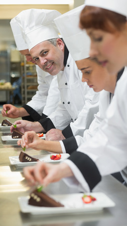 Team of chefs in a row garnishing dessert plates one smiling at camera in busy kitchen photo